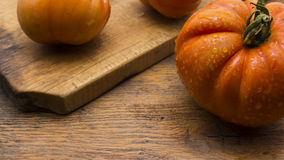 Tomatoes on wooden chopping board. And table Royalty Free Stock Photo