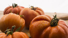 Tomatoes on wooden chopping board. And table Royalty Free Stock Photos