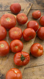 Tomatoes on wooden chopping board. And table Royalty Free Stock Image