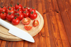 Tomatoes on wooden cutting board being cut in half by white knife Royalty Free Stock Photography