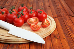 Tomatoes on wooden cutting board being cut in half by white knife Stock Photos