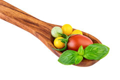 Tomatoes on wooden spoon with basil leaf cooking concept Royalty Free Stock Photography