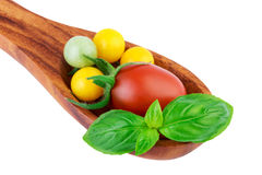 Tomatoes on wooden spoon with basil leaf fresh vegetables cooking concept Royalty Free Stock Images