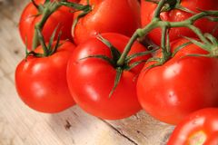 Tomatoes on wooden surface Royalty Free Stock Images