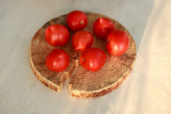 Tomatoes on a wooden surface Royalty Free Stock Image