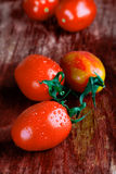 Tomatoes on wooden table Royalty Free Stock Photos