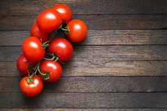 Tomatoes on wooden table with copy space. Fresh red tomatoes on branch on dark brown wooden table. Copy space. Oak texture. Top view. Horizontal orientation royalty free stock photography