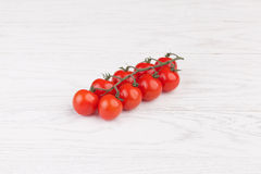 Tomatoes on a wooden table. Fresh cherry tomatoes on branch on a wooden table Royalty Free Stock Photo