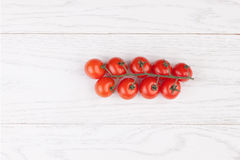 Tomatoes on a wooden table. Fresh cherry tomatoes on branch on a wooden table Stock Photography