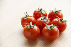 Tomatoes on wooden table Stock Images