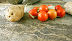 Tomatoes 10. Tomatoes on wooden table with rocks Royalty Free Stock Image