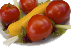 Tomatoes and zucchini plate isolated Stock Images