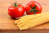 Tomatoesl and uncooked spaghetti Royalty Free Stock Photo