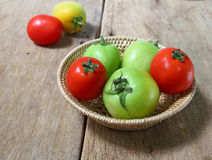 Tomatos in bamboo basket on wood table Royalty Free Stock Images
