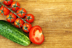 Tomatos and cucumber on wooden board Royalty Free Stock Photo