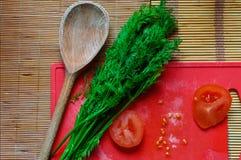 Tomatos, dill, spone, kitchen - cooking. Stock Photos