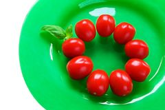 Tomatos on a green plate with basil. Circle of ripe red tomatoes an a glass plate with basil Stock Photos