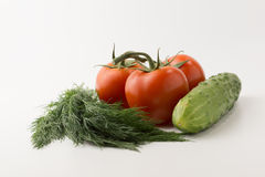 Tomatos and green vegetable. Some small red tomatoes with a green branch and a cucumber with parsley and onions on a white background Royalty Free Stock Images