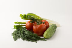 Tomatos and green vegetable. Some small red tomatoes with a green branch and a cucumber with parsley and onions on a white background Royalty Free Stock Image