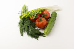 Tomatos and green vegetable. Some small red tomatoes with a green branch and a cucumber with parsley and onions on a white background Royalty Free Stock Photo