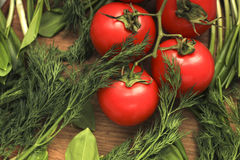 Tomatos. With greenstuff on a cutting board Stock Photos