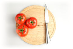 Tomatos and knife on plate Royalty Free Stock Photography