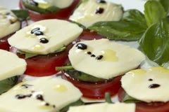 Tomatos, mozzarella and basil with olive oil. Stock Photos