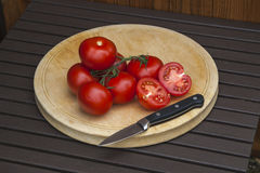 Tomatos, red, ripe and fresh, on cutting board with knife. Stock Photos