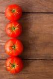 Tomatos on rustic wood background Stock Photos