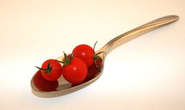 Tomatos on a Spoon. Cherry tomatos on the end of a spoon Stock Photography