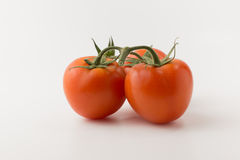 The tomatos on white background. Some small red tomatoes with a green branch on a white background Royalty Free Stock Photos