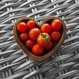 Tomatos - Wooden Heart Shaped Bowl. Tomatos in Wooden Heart Shaped Bowl, Wicker Background royalty free stock photos