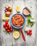 Tomatsås med på burk tonfisk i lantlig kruka med grönsaker och kryddor arkivbild