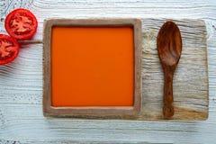 Tomatsås på fyrkantigt maträtt- och vitträ Royaltyfria Bilder