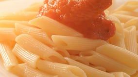 Tomatsås som hälls på pennepasta stock video