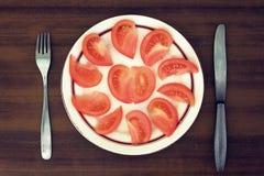 Tomatsegment på en platta Tona i tappningstil Arkivfoto