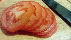 Tomatskivor och kniv på brädet arkivfoto