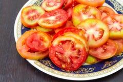 Tomatskivor på en platta som förläggas på en trätabell Fokus på Arkivfoton