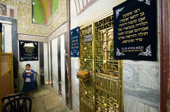 Tomb of Abraham. HEBRON, ISRAEL, 10 OCT, 2014: A young girl is reading the torah close to the tomb of patriarch Abraham behind the green iron doors. The tombs of Stock Image