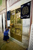 Tomb of Abraham. HEBRON, ISRAEL, 10 OCT, 2014: A young girl is watching through the bars of an iron door to the tomb of patriarch Abraham. The tombs of the stock photography