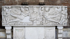 Tomb Artifact (Campo Santo - Pisa). This is a detail photo of an old roman tomb, with a sculpture relief representation in front, depicting a scene from history Stock Photography