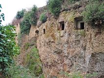Tomb entrances in the cliff wall of a Via Cava, an ancient Etruscan road carved through tufo cliffs in Tuscany. Etruscan tombs carved into the wall of an ancient royalty free stock images