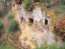 Tomb entrances in the cliff wall of a Via Cava, an ancient Etruscan road carved through tufo cliffs in Tuscany. Etruscan tombs carved into the wall of an ancient Stock Photography