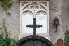 The cross of the wrought iron fence in the foreground, and an old gravestone from the 19th century in the background royalty free stock photography