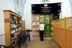 Tomb of Jacob. HEBRON, ISRAEL, 10 OCT, 2014: A jewish man is praying in front of the tomb of patriarch Jacob, behind the green iron door. The tombs of the Royalty Free Stock Photos