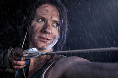 Tomb Raider. Portrait of woman, Lara Croft-like character. Rise of the Tomb Raider. Woman dressed up as Lara Croft stands in the rain, aiming with a bow and Stock Photos