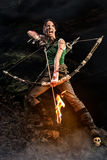 Tomb Raider. Portrait of woman, Lara Croft-like character. Rise of the Tomb Raider. screaming woman dressed up as Lara Croft holds a bow and pulls the bowstring Royalty Free Stock Images