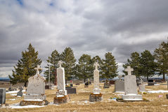 Country Cemetery with pine trees and clouds drama Royalty Free Stock Photo
