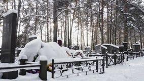 Tomba cristiana o ortodossa di Snowy con la corona funerea in cimitero o in cimitero nell'inverno in foresta video d archivio