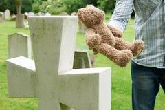 Tomba di Placing Teddy Bear On Child del padre in cimitero Fotografie Stock